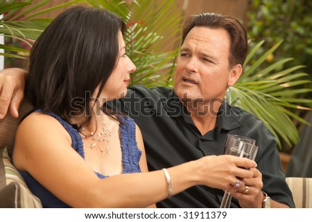 Attractive Hispanic and Caucasian Couple Drinking Wine Outside. - stock photo