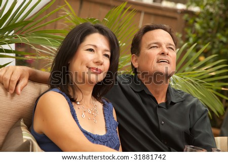 Attractive Hispanic and Caucasian Couple Socializing Outside. - stock photo