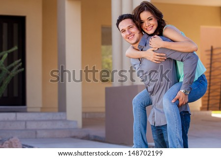 Attractive Hispanic couple arriving to their brand new house and smiling - stock photo