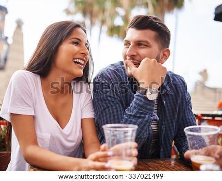 attractive hispanic couple drinking beer and having fun at outdoor restaurant - stock photo