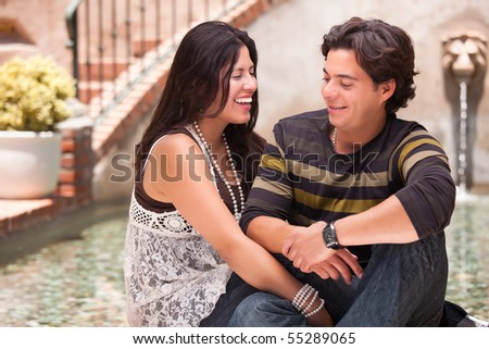 Attractive Hispanic Couple Ejoying Each Other At A Fountain. - stock photo