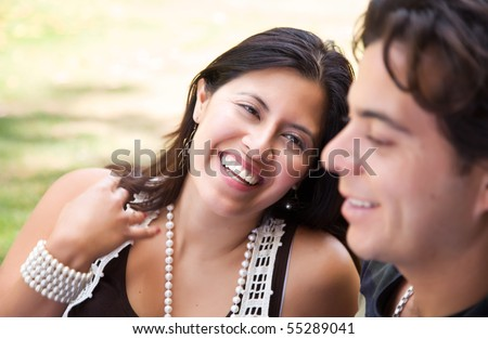 Attractive Hispanic Couple Enjoying Themselves At The Park. - stock photo