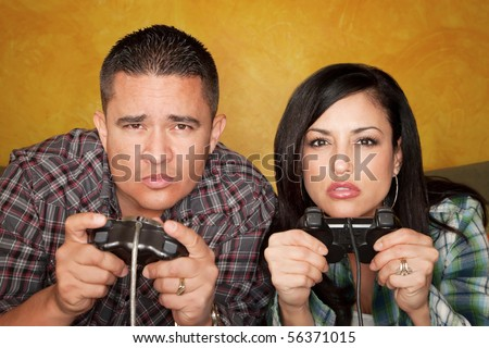 Attractive Hispanic Couple Playing a Video Game with Hand held Controllers - stock photo