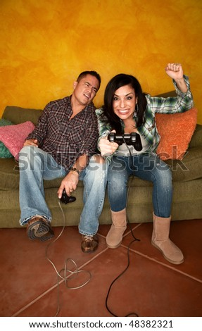 Attractive Hispanic Couple Playing a Video Game with Handheld Controllers - stock photo