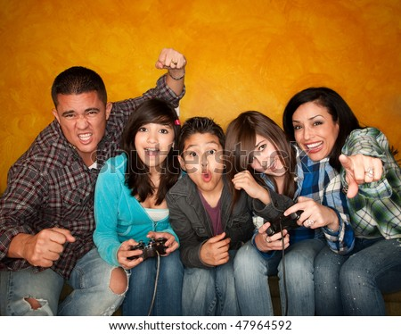 Attractive Hispanic Family on Couch Playing a Video Game - stock photo