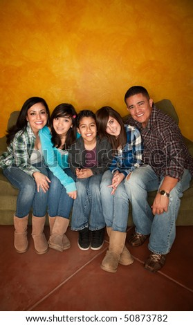 Attractive Hispanic Family Sitting on a Green Couch - stock photo
