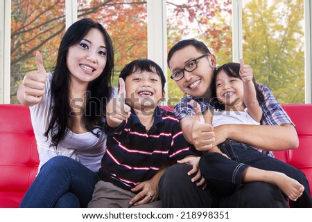 Attractive hispanic family smiling and showing thumbs-up at camera with autumn background on the window - stock photo