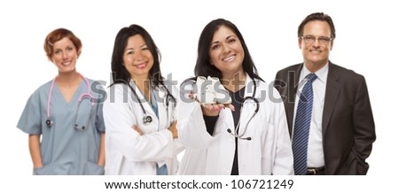 Attractive Hispanic Female Doctor or Nurse Holding Out Baby Shoes and Support Staff Behind Isolated on a White Background. - stock photo