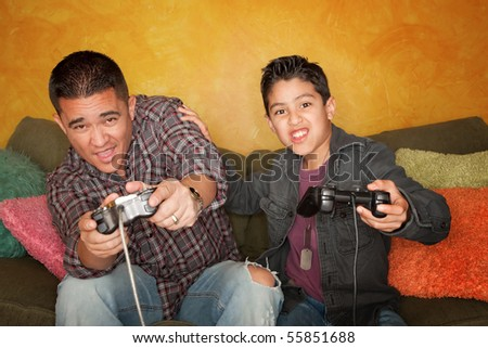 Attractive Hispanic Man and Boy Playing a Video Game with Hand held Controllers - stock photo