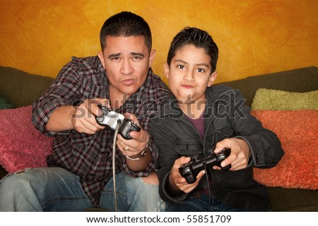 Attractive Hispanic Man and Boy Playing a Video Game with Handheld Controllers - stock photo