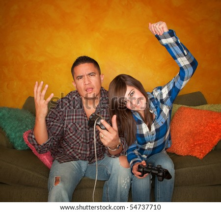 Attractive Hispanic Man and Girl Playing a Video Game with Handheld Controllers - stock photo