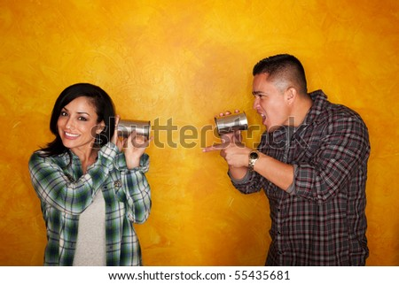 Attractive Hispanic man and woman communicate through tin cans - stock photo