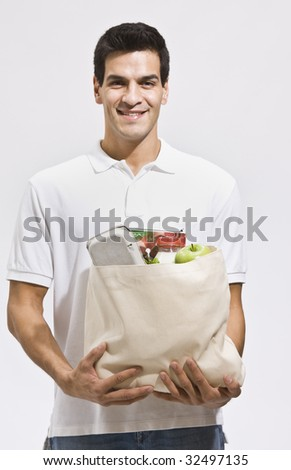 Attractive hispanic man holding a bag of groceries and smiling at the camera. Vertically framed shot.