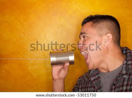 Attractive Hispanic man with tin can telephone - stock photo