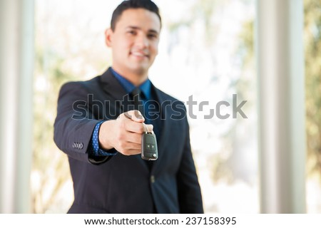 Attractive Hispanic salesman handing over the keys of a new car. Focus on keys - stock photo