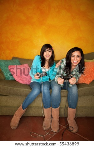 Attractive Hispanic Woman and Girl Playing a Video Game with Handheld Controllers - stock photo