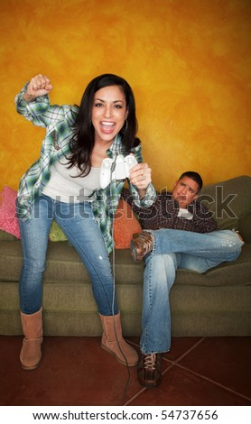 Attractive Hispanic woman playing video game while bored partner watches - stock photo