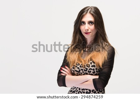 Attractive hispanic woman with crossed arms looking ver serÃ??ous with big bright eyes - stock photo