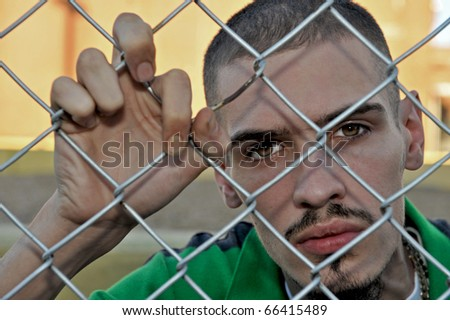 Attractive Hispanic young man revealing his anger and depression while leaning against a chain link fence.