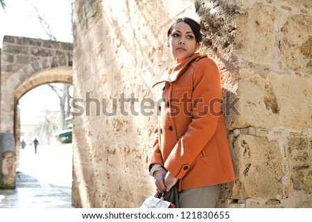 Attractive hispanic young woman leaning on an old stone wall while visiting a sight on vacations, holding shopping bags and being thoughtful. - stock photo