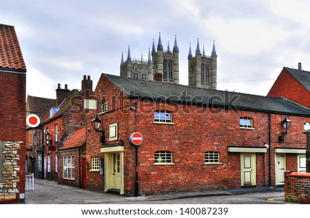 Attractive historic red- brick houses and cobbled streets in the neighborhood of Lincoln Cathedral, England. Cathedral towers in the background. Tone-mapped to enhance the detail of the brickwork. - stock photo