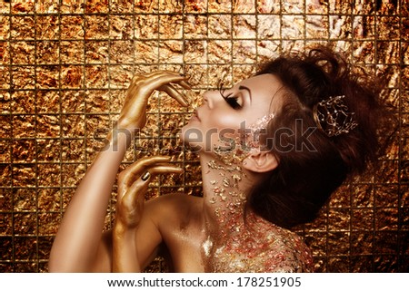 Attractive hot brunette with beautiful golden makeup and gold caramel painted hands is posing in front of abstract golden background - stock photo