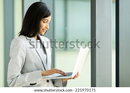 attractive indian businesswoman working on laptop in office - stock photo