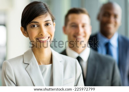 attractive indian female business leader with colleagues standing on background