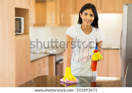 attractive indian housewife cleaning the kitchen - stock photo