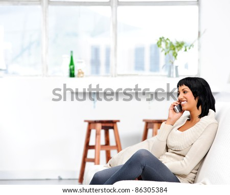 Attractive indian woman at home, talking to her friend over the phone - stock photo