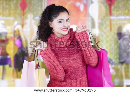 Attractive indian woman wearing sweater and carrying shopping bags in the shopping center - stock photo