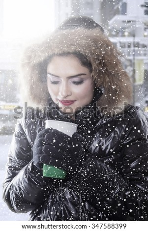 Attractive indian woman wearing winter jacket and enjoy hot coffee in snowy day - stock photo
