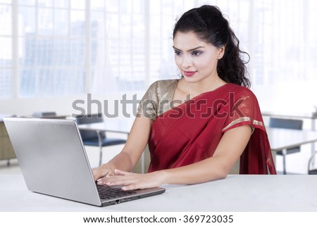Attractive indian young businesswoman wearing traditional clothes and working with laptop computer - stock photo