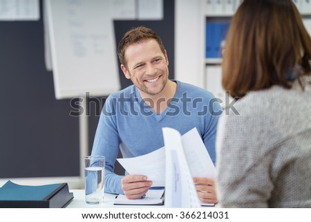 Attractive informal young businessman with a friendly smile discussing paperwork with a female colleague in the office