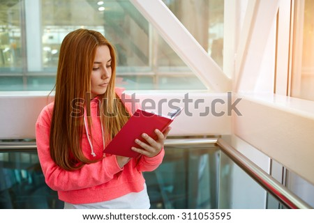 Attractive intelligent college student reading workbook or notebook while standing in the hallway of a modern building, stylish young hipster girl preparing for the exam at the university indoors - stock photo