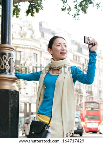 Attractive Japanese tourist woman sightseeing in a classic architecture street in the destination city of London, taking pictures with a digital photo camera during a sunny day on vacation, outdoors. - stock photo