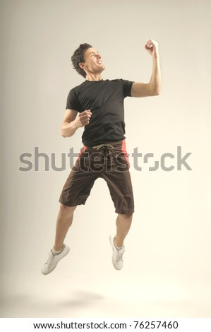 Attractive jumping man in a sport outfit and sport shoes