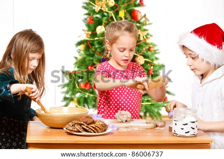 Attractive kids busy making Christmas cookies