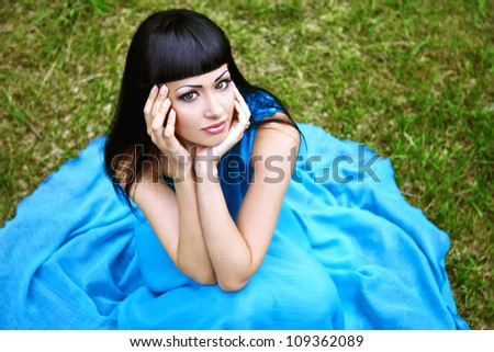 Attractive lady in blue dress on grass summertime - stock photo