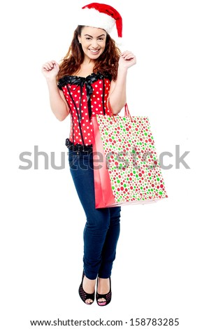 Attractive lady in santa cap, holding shopping bag - stock photo