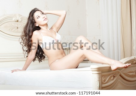 Attractive lady lying and pamepring in bedroom