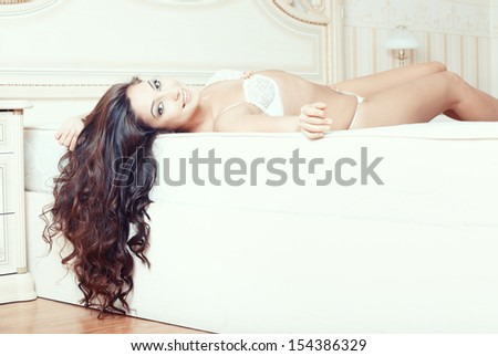Attractive lady lying and pamepring in bedroom - stock photo