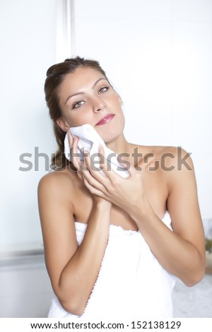 attractive lady removing her make up and looking at camera - stock photo