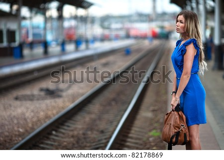attractive lady waiting train on the platform of railway station - stock photo