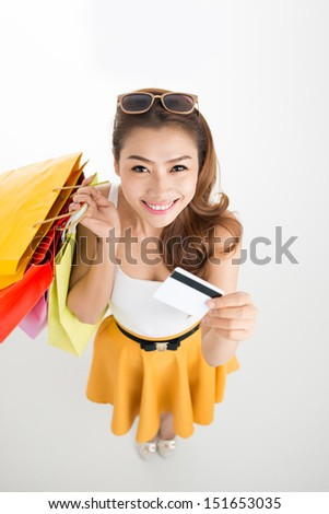 Attractive lady with shopping bags and a credit card over a white background viewed below - stock photo