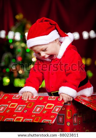 Attractive laughing baby in Santa costume - stock photo