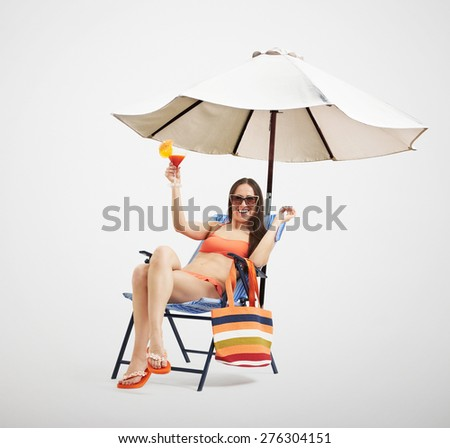 attractive laughing woman in bikini and sunglasses relaxing on the beach chair and holding cocktail under beach umbrella over light background - stock photo