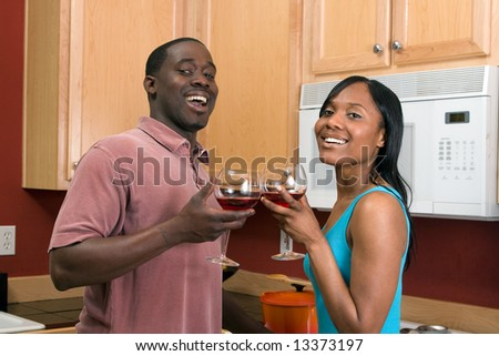 Attractive laughing young African American couple standing in a kitchen clinking wine glasses, in a toast.  Horizontally framed, close cropped, shot with the man and woman looking at the camera.
