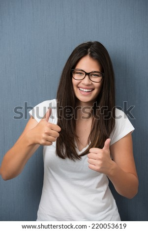 Attractive laughing young teenage girl student wearing glasses giving a thumbs up of approval and success as she stands in front of a blank chalkboard - stock photo