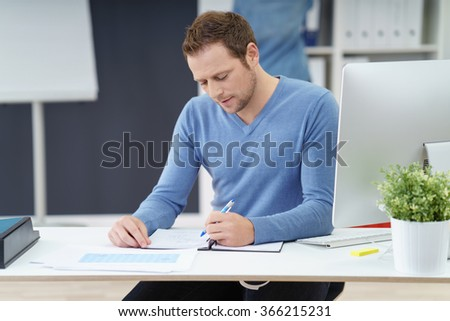 Attractive left handed businessman sitting at a table doing paperwork in the office with a serious expression - stock photo